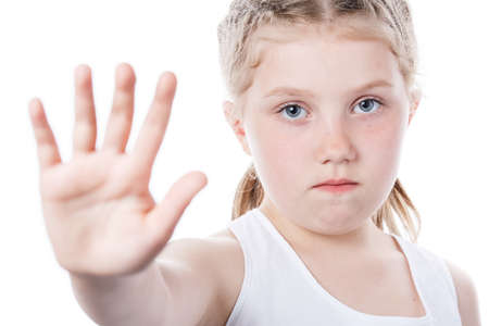 cute little girl showing hand stop sign isolated on white background, child protection