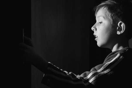 Child open door and bright lit illuminate him. Surprised boy saw something. Door to knowledge. black and white.