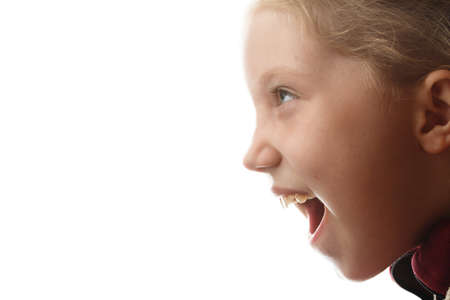 Close-up portrait of a little girl screaming loudly on an isolated white background, a lot of clean free space, illuminated by office light in the back Фото со стока