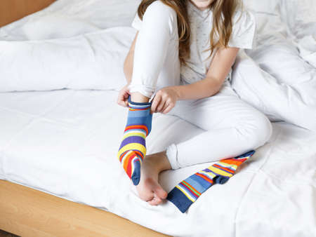 little cute girl gets ready for bed puts on striped socks, on the bed the child changes clothes