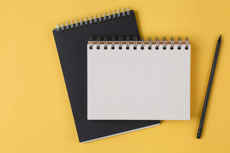 school open notebook with a pencil on a yellow background top view, blank sheet for writing purposes, business concept flat lay