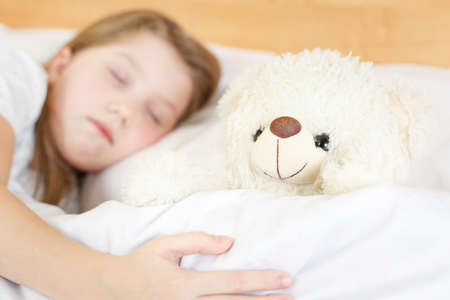 cute little girl sleeping with soft toy on clean white soft bed, healthy sleep in child is good health