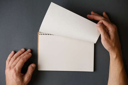 Male hands turn over a page of a spiral notepad on a gray background vertical photo.