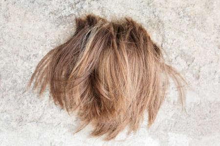 Cut off light brown hair lies on the floor after cutting. 版權商用圖片