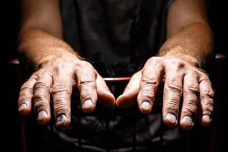 Male weary hands, palms down on a black isolated background. Concept of Hope and Support.