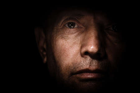 Portrait of an elderly man with brown eyes on a black background view from close up.