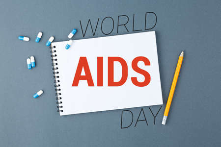 Open notebook with clear page with yellow pencil and capsule pills on grey background. First december World AIDS Day Cancer Control concept Symbolizing day of AIDS and HIV. Top view.
