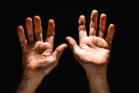 Hands reaching upwards with open palm on black isolated background. Concept of Hope and Support.