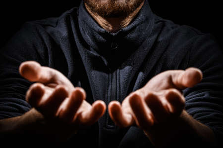 Male weary hands, palms up on a black isolated background. Concept of Hope and Support. Stockfoto
