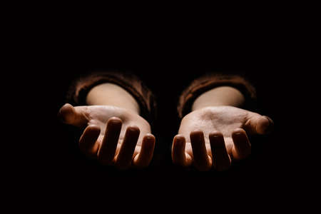 Female weary hands, palms up on a black isolated background. Concept of Hope and Support.