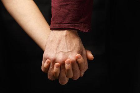 male hand holds female hand on dark background