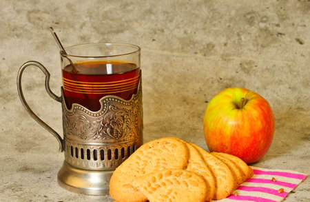 Tea in a Cup holder with cookies and an Apple on a gray background. Good nutrition. Space for text. Lifestyle