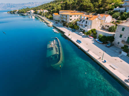 Sunken ship offshore Aerial - High ange view of village. Small Adriatic town