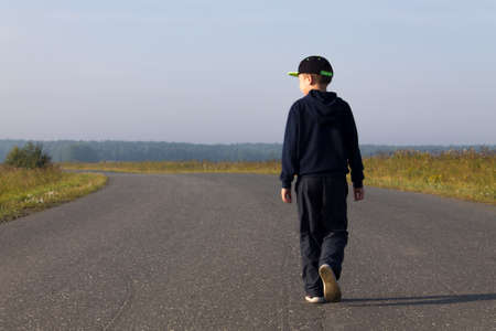 A boy in a cap and a sweatshirt goes forward in the middle of the highway in the field