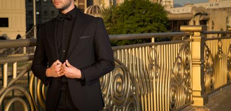 黄金のフェンスの横にポーズ、黒のスーツで男性モデル