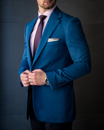 Male model in a suit posing in front of a grey wall