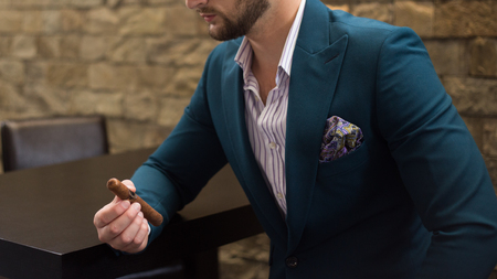 Male model in a suit posing with a cigar in his hand Imagens