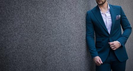 Mannelijk model in een pak poseren naast een grijze muur