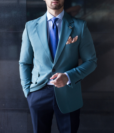 Male model in suit posing in front of a black wall