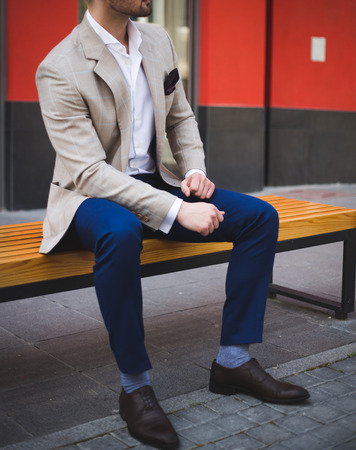 ベンチに座っているスーツで男性モデル