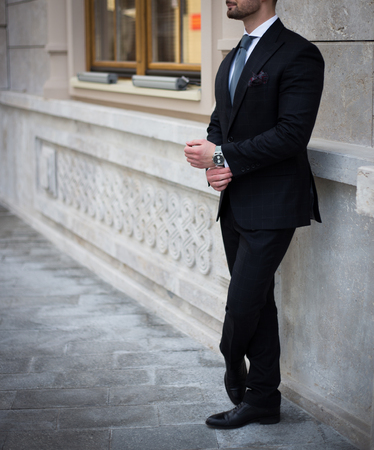 Male model in a black suit posing outdoors