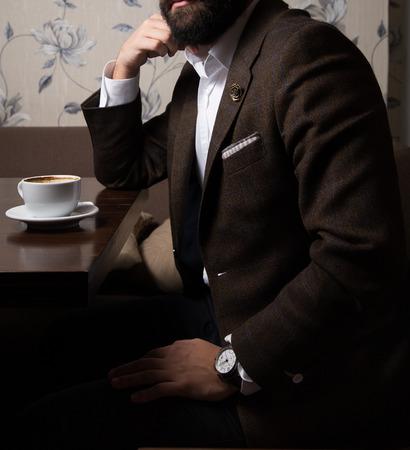 Male model in a suit drinking coffee