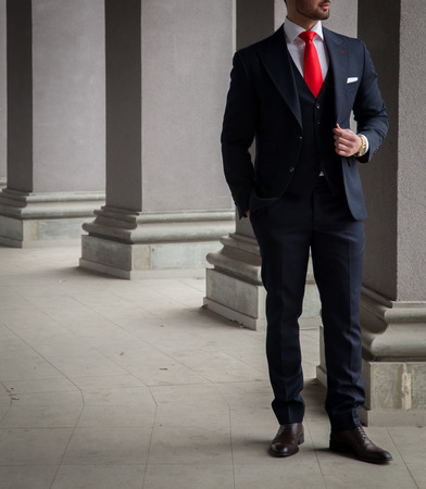 Male model in a suit posing in front of grey colums