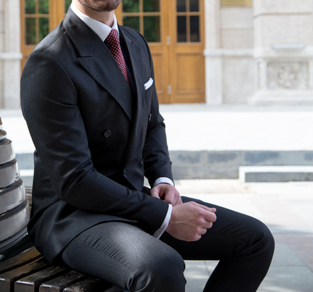 Male model in a suit sitting on a bench Imagens