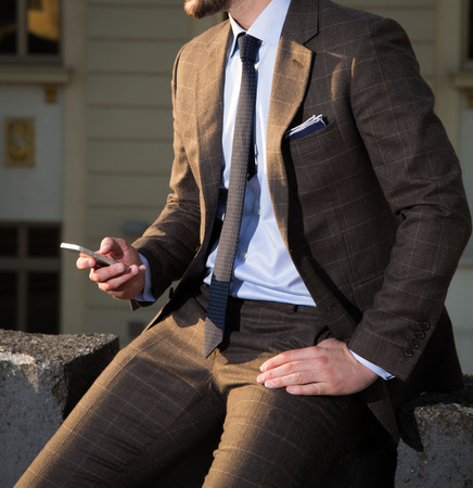 Male model in a suit posing outdoors holding mobile phone