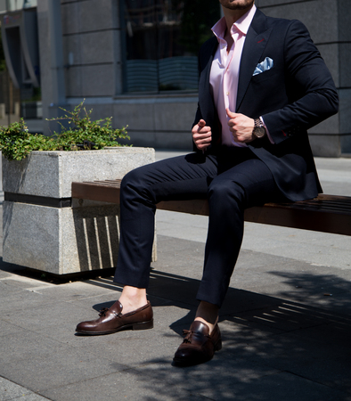 Male model in a suit posing on  bench
