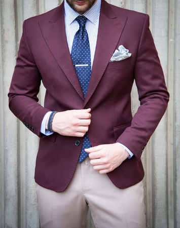 Male model in a suit posing in front of a concrete wall Imagens