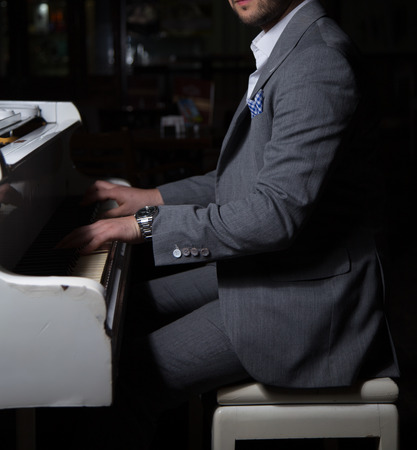 Male model in a suit posing with a piano