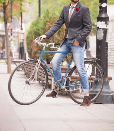 Male model in a suit posing on a bike. Imagens