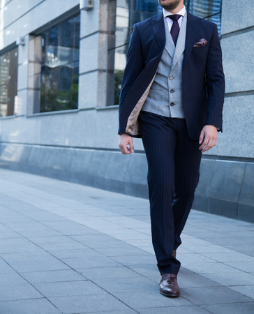 Male model in a suit posing outdoors.