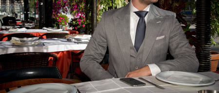 Male model in a suit posing in a restaurant.