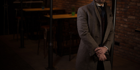 Male model in a suit with a coat posing in a bar