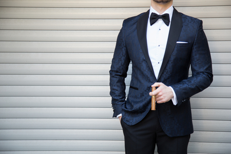 Male model in a tuxedo and a cigar posing