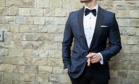 Male model in a tuxedo with a cigar posing in front of a brick wall Imagens