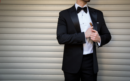 Male model in a tuxedo with a cigar posing