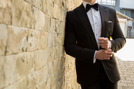 Male model in a suit posing next to a brick wall
