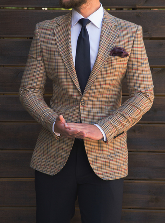 Male model in a suit posing in front of a wooden wall Imagens