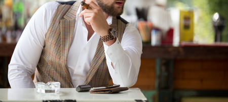 Male model in a vest with a cigar posing outdoors