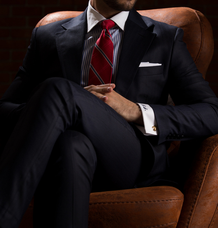 Male model in a suit sitting in a leather armchair