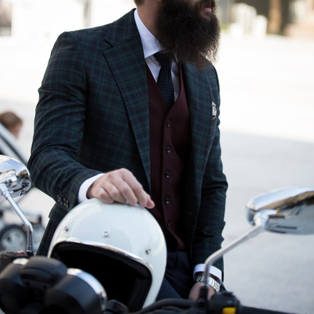 Male model in a suit posing on a motorcycle