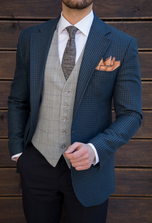Male model in a three part suit posing in front of a wooden wall up-close