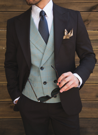 Male model in a three part suit posing in front of a wooden wall Imagens