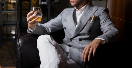 Male model in a suit, holding a drink and posing Imagens