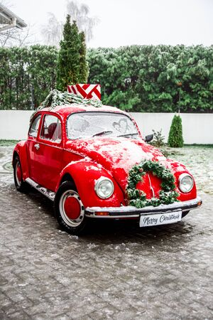 Christmas concept retro Santa Claus red car with christmas wreath with present boxes on top. Winter snow Stock fotó