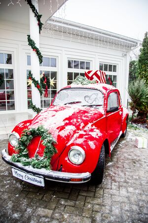 Christmas retro red car with present boxes on top. White house on background