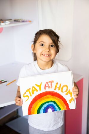 Stay at home due coronavirus pandemic concept. Little girl paints a rainbow on stay at home poster. Chase the rainbow flashmob. Positive activities during quarantine and staying at home. COVID - 2019.
